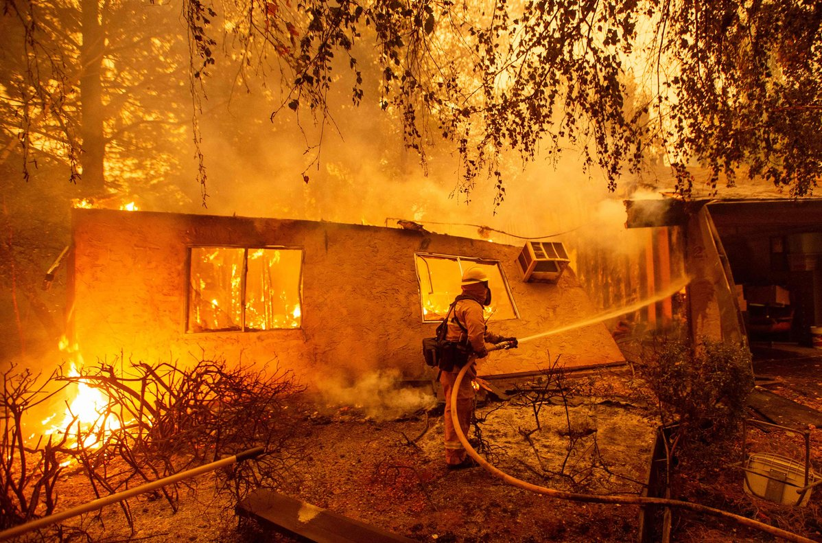 TOPSHOT - Firefighters battle flames at a burning apartment complex in Paradise, north of Sacramento, California on November 09, 2018. - A rapidly spreading, late-season wildfire in northern California has burned 20,000 acres of land and prompted authorities to issue evacuation orders for thousands of people. As many as 1000 homes, a hospital, a Safeway store and scores of other structures have burned in the area as the Camp fire tore through the region. (Photo by Josh Edelson / AFP)