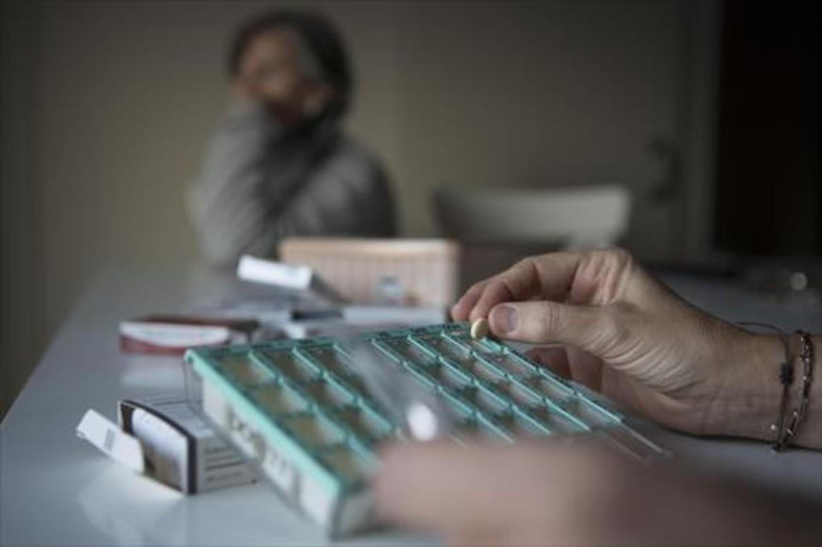 Un paciente coge una píldora de una caja de fármacos.