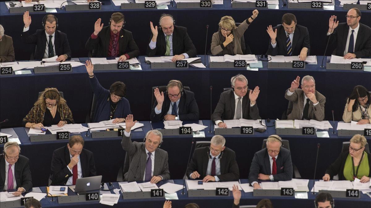 Varios eurodiputados votan a mano alzada en un pleno de la Eurocámara en una foto de archivo.