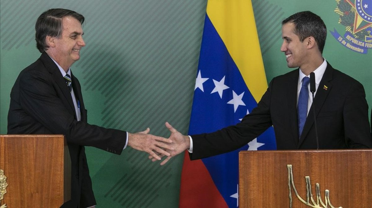 El presidente de Brasil, Jair Bolsonaro (izquierda), y el líder opositor y autoproclamado presidente venezolano, Juan Guaidó, se saludan durante el encuentrpo que mantuvieron este jueves en Brasilia.