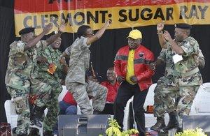 El presidente sudafricano y líder del Congreso Nacional Africano, Cyril Ramaphosa (con chaqueta roja) bailacon unos militaresdurante un mitin de su partido en la ciudad de Durban.