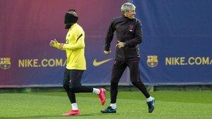 Quique Setién, detrás de Arturo Vidal, que corre con la vista tapadadurante un ejercicio previo al entrenamiento del Barça.