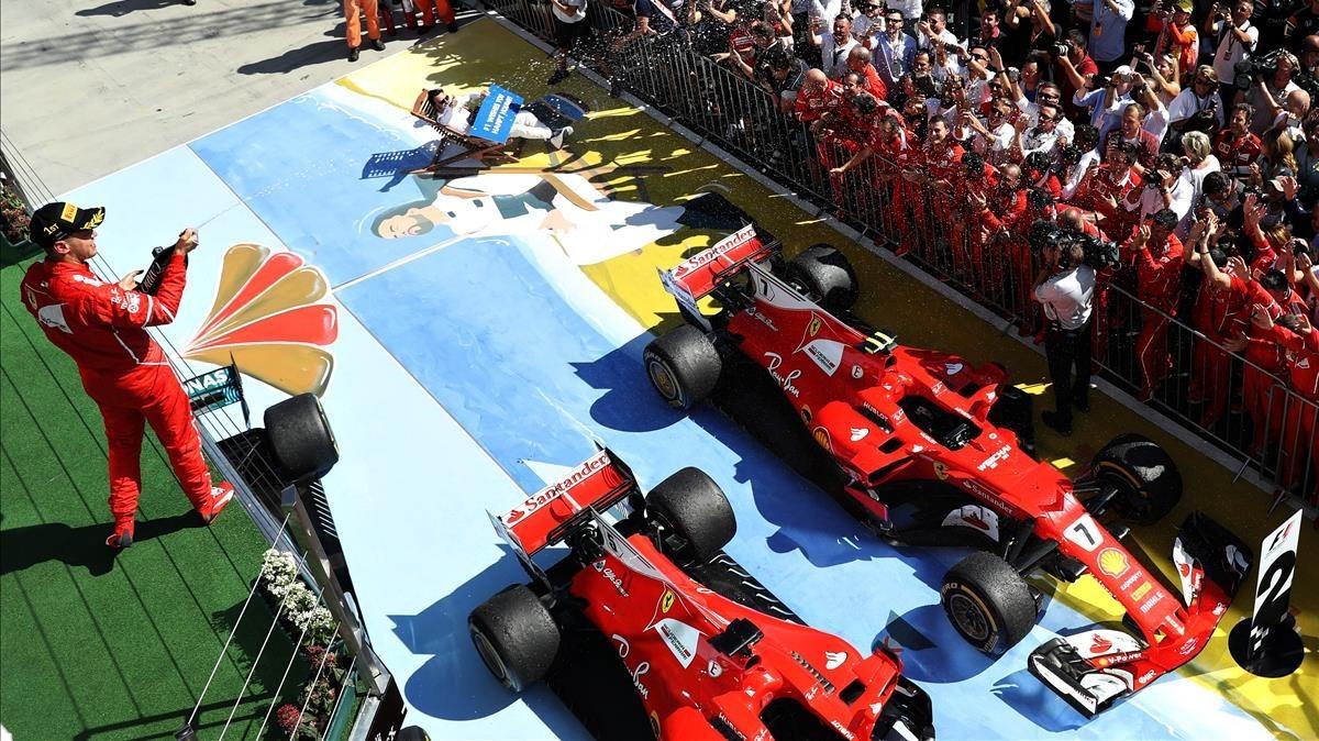 Sebastian Vettel celebra la victoria en el podio de Hungaroring mientras Alonso posa sobre un mural con la icónica imagen en una tumbona de Brasil-2015.