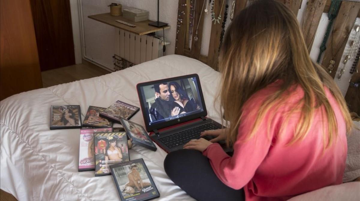 Una joven entra en una web de videos pornográficos en la habitación de su casa.