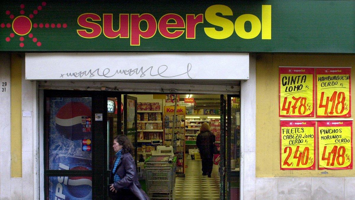 Una cliente sale de un supermercado SuperSol, en una centrica calle de Sevilla.