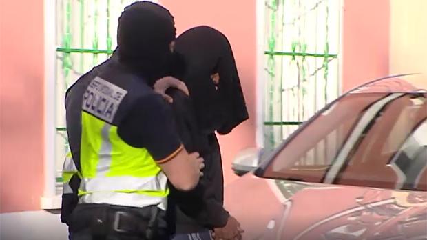 Trasllat del gihadista detingut a Madrid després del registre a la seva vivenda. El presumpte islamista ha sortit de casa seva amb el cap tapat.