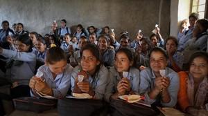 Unas jóvenes inspeccionan las copas menstruales en la ciudad nepalí de Kalagaun.