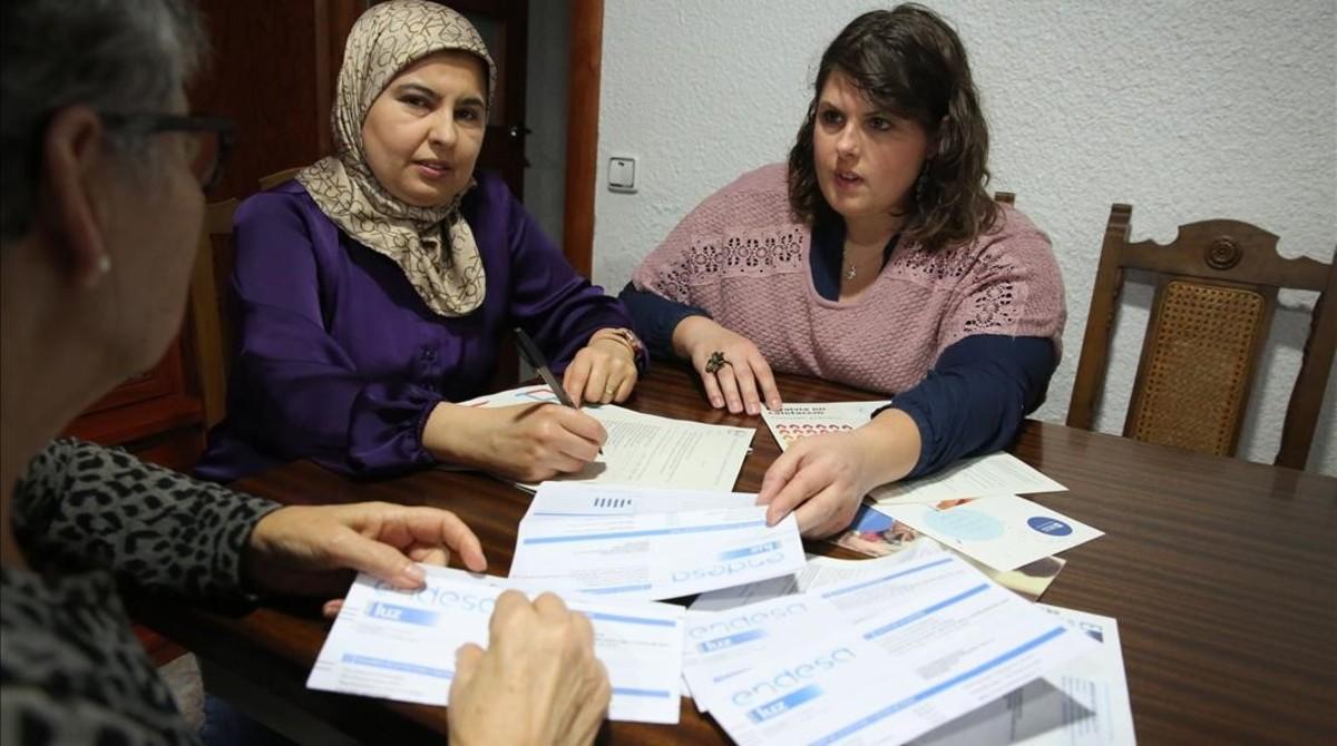 Souad y Sara miran las facturas de una vecina en elsalón de su casa, la semana pasada.