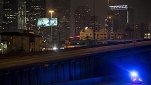 Un coche de policía patrulla las calles de Houston después del anuncio del toque de queda anunciado por el alcaldede la ciudad, Sylvester Turner.