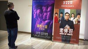 Un cliente de un cine chino observa un cartel de la película Bohemian Rhapsody en Pekín.