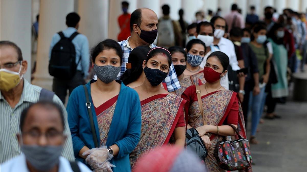 Personas con mascarillas protectoras en una estación de metro, en medio de la propagación de la enfermedad del coronavirus, en Nueva Delhi.