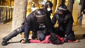 Los Mossos inmovilizan a uno de los detenidos en los disturbios del viernes en Barcelona.
