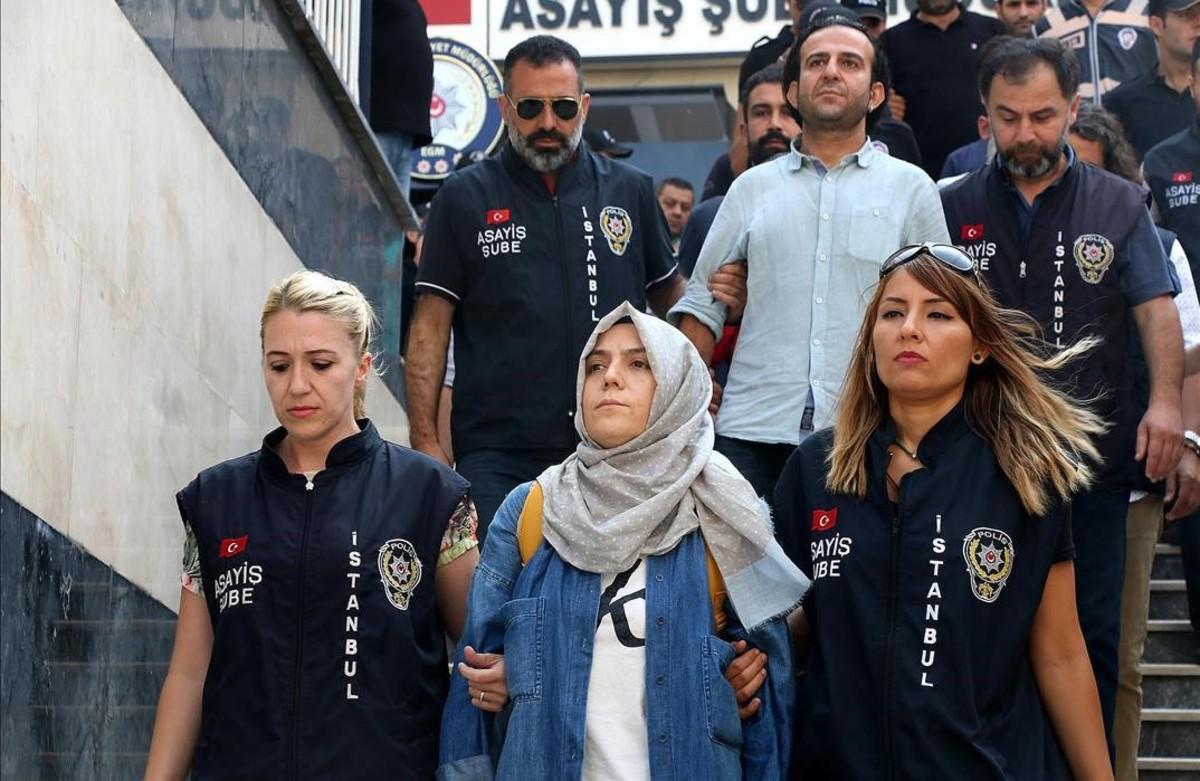 La policía escolta a una periodista detenida ante el juez en Estambul.