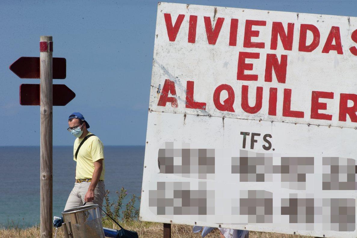 Un hombre camina junto a un cartel de viviendas en alquiler en A Mariña (Lugo/Galicia)