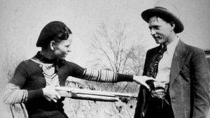 Bonnie Parker y Clyde Barrow bromean con sus armas en una foto de 1932.