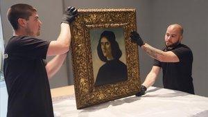 Dos operarios sostienen el cuadro 'El Retrato de Michele Marullo Tarcaniotes', de Sandro Boticelli, este 3 de octubre