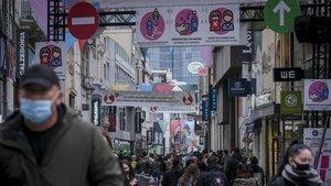 Ciudadanos con mascarila pasean por una calle comercial de Brusleas, este miércoles.