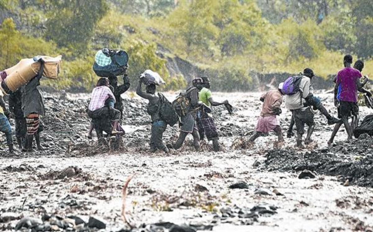 Ciudadanos haitianos intentan cruzar el río La Digue después de que se hundiera el puente que lo cruzaba.