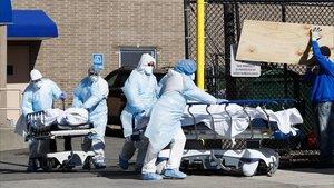 Un grupo de sanitarios transportan los cuerpos sin vida de dos personas a una morgue habilitada en el exterior delWyckoff Heights Medical CenterenBrooklyn, Nueva York.
