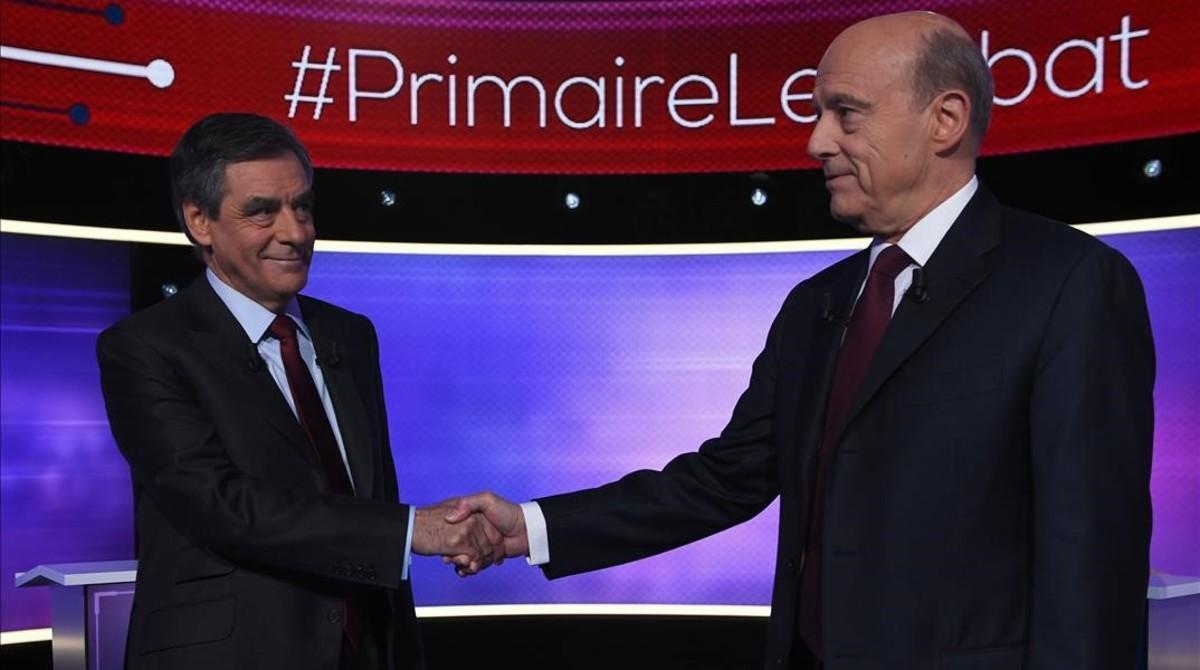 Fillon (izquierda) y Juppé se dan la mano antes del debate televisado, este jueves, en París.