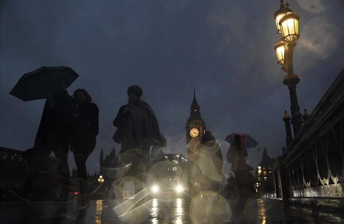 Gent camina pel pont de Westminster sota la pluja a conseqüència d'una vaga convocada pels sindicats del metro de Londres.