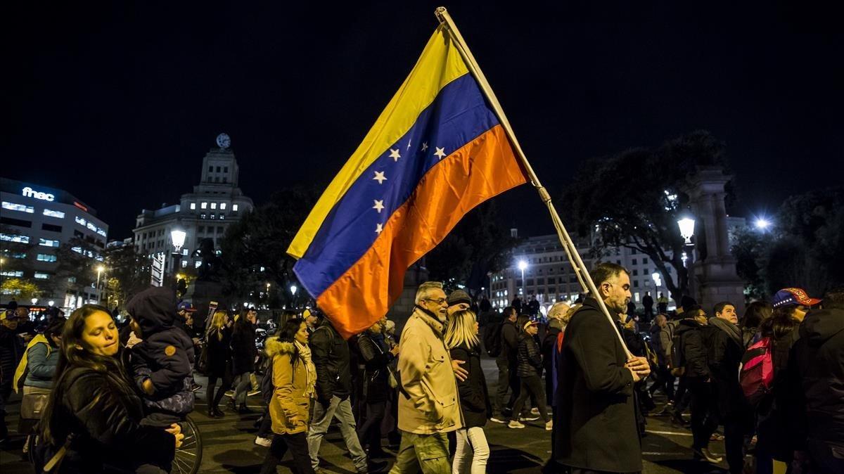 Un hombre enarbola la bandera venezolana al paso de la marcha por la plaza de Catalunya.