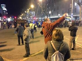 Un turista se hace una selfie al paso del ataud policial, en plaza de Catalunya.