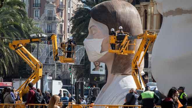 Las Fallas de Valencia, aplazadas por el coronavirus. En la imagen, la falla municipal ataviada con una mascarilla, tras la suspensión de la fiesta.