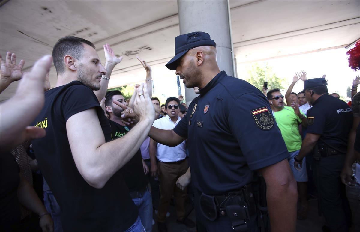 Un momento de tensión entre taxistas y la policía a la puerta del Ministerio de Fomento, cuando un huelguista hja lanzado un objeto contra un taxi que funcionaba en servicios mínimos.
