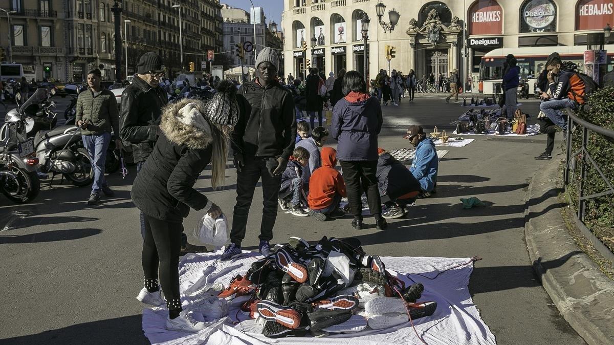 Manteros en la plaza deCatalunya.