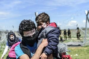 Un padre coge en brazos a su hijo, durante los ataques con gases lacrimógenos en la frontera de Macedonia, este domingo.