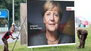 Retirada de un cartel electoral de Angela Merkel en Berlín.