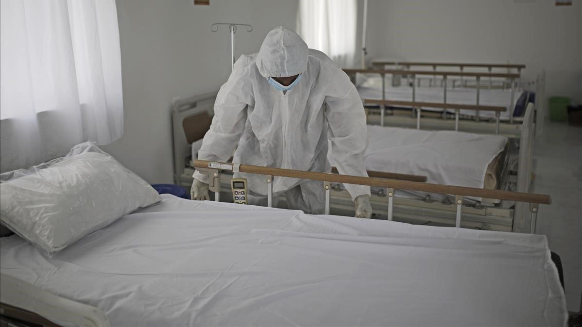 Un sanitario hace la cama para personas en cuarentena por coronavirus, el pasado domingo.