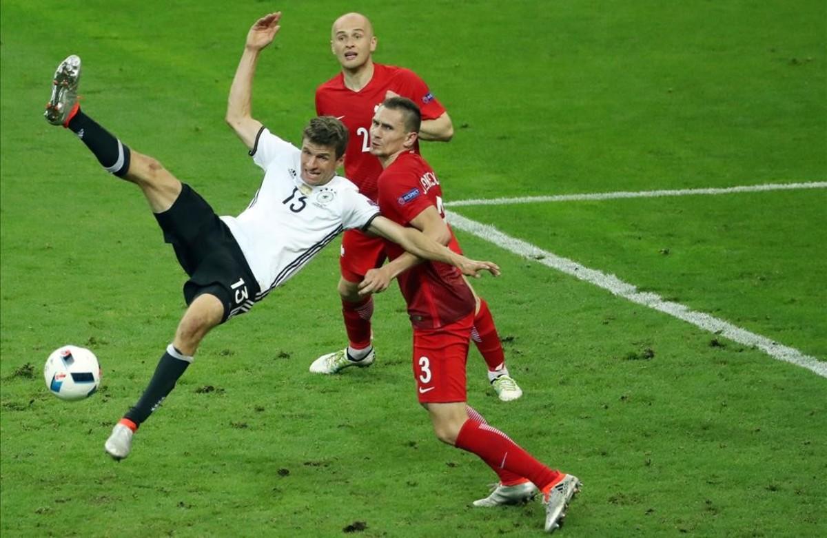 Thomas Mueller lucha conArtur Jedrzejczykdurante el partido entre Alemania y Polonia.