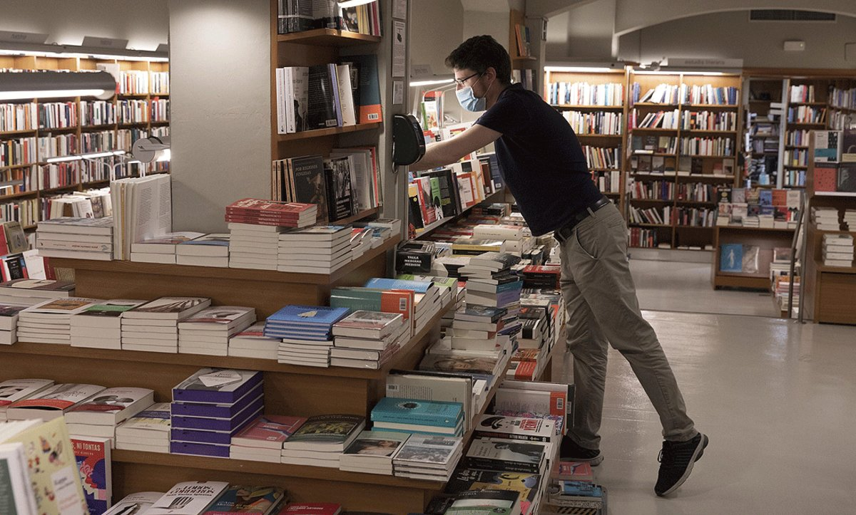 Un trabajador deLaie prepara la librería de la calle de Pau Claris de Barcelona para la reapertura parcial que se inicia el 4 de abril, este miércoles.