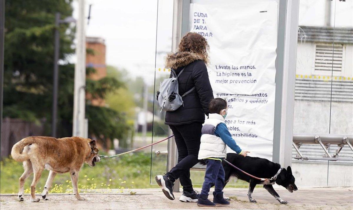 Una mujer pasea con su hijo y sus perros en Boadilla del Monte (Madrid), el 16 de abril.