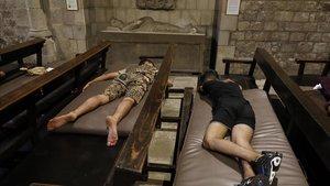 Unos niños duermen sobre los bancos de la iglesia de Santa Anna, en el barrio Gòtic de Barcelona.