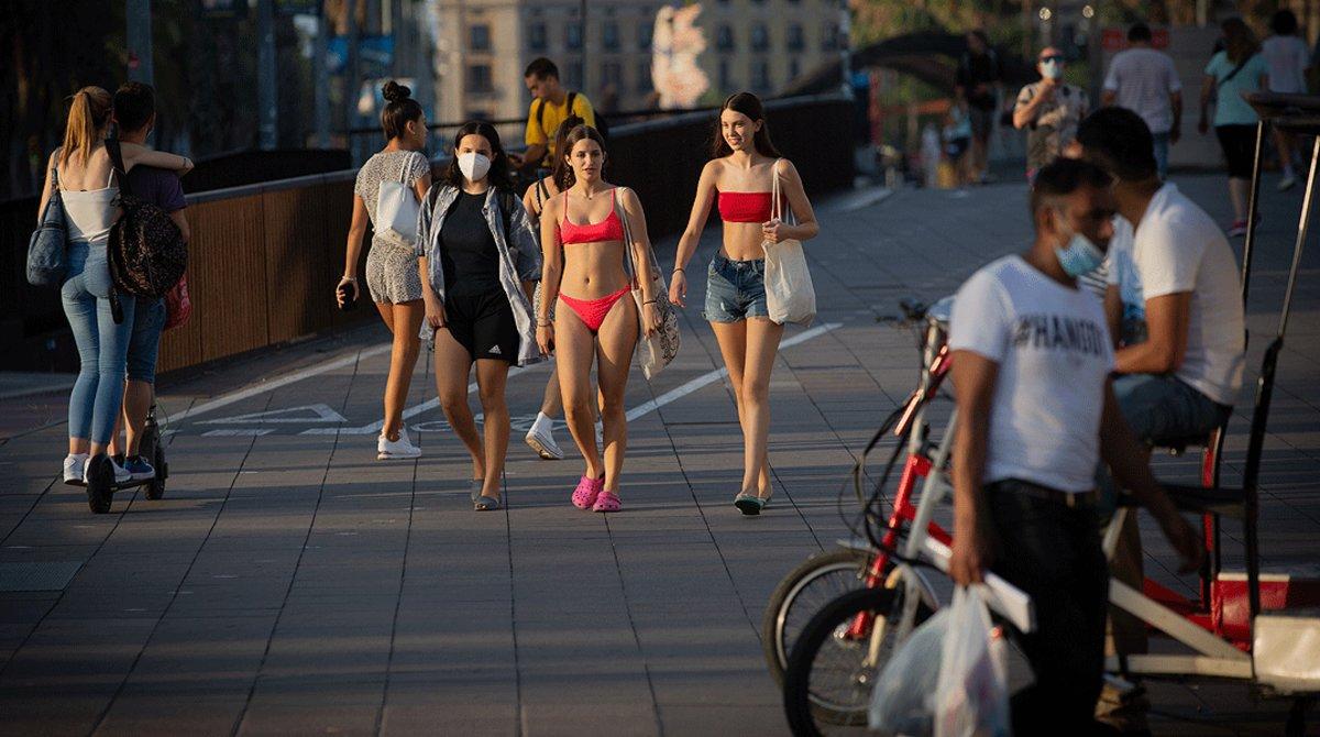 Varios jóvenes sin mascarilla o con ella mal puesta pasean por el centro de Barcelona, este miércoles 29 de julio.