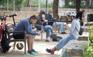 Vecinos del barrio de la Sagrada Família de Barcelona en un parque público.