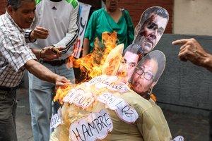 La quema de un muñeco con la foto de Nicolas Maduro y otros políticos de su gobierno.