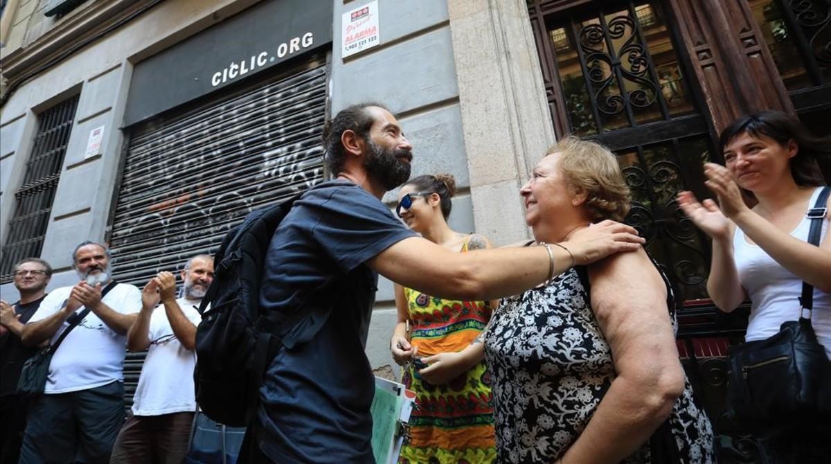 David Cabrera se abraza con una de las vecinas de la finca tras parar el desahucio del videoclub.