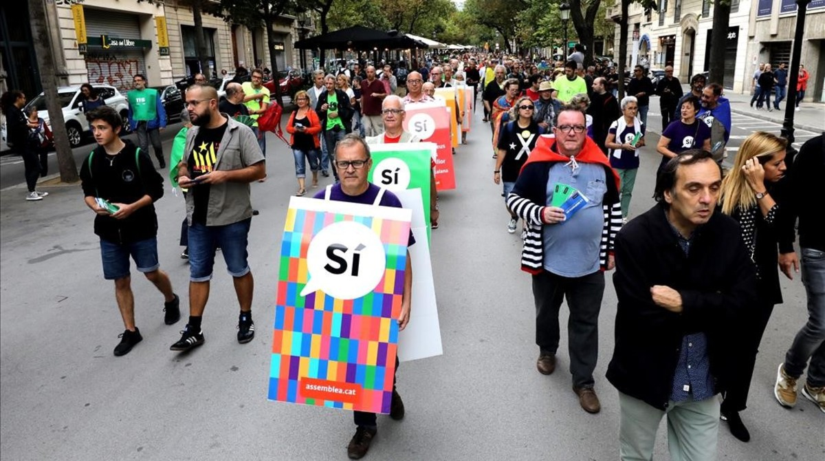 Carteles humanos con propaganda en favor del sí al referéndum en el centro de Barcelona.