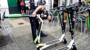 Agentes de la policía local de Valencia retiran unos patinetes eléctricos de alquiler.
