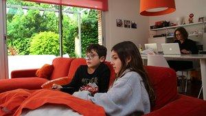 Irene y Mauro Bagen Guillem, de 12 y 9 años, en su casa en Barcelona mirando la tele. Al fondo, su madre teletrabajando.