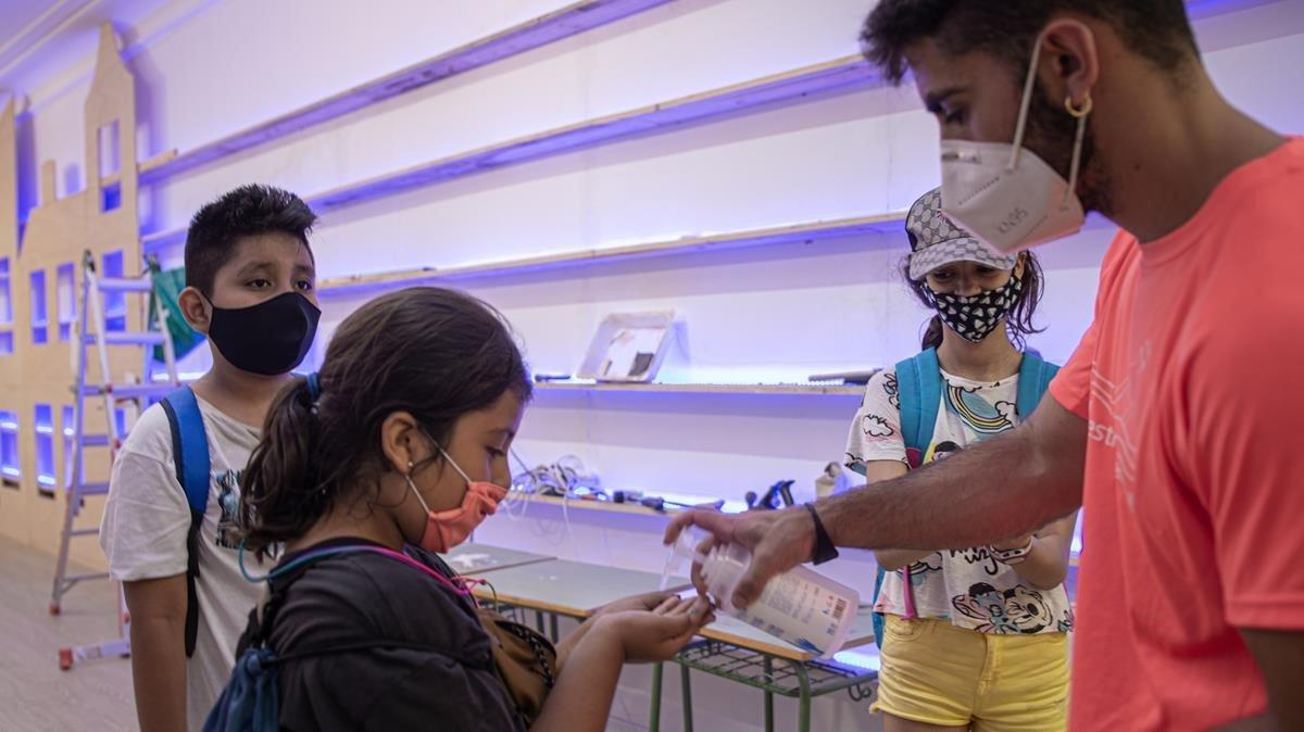 Un grupo de niños se lava las manos antes de entrar a las actividades de un casal de verano, organizado en la escuela Octavio Paz de Barcelona.