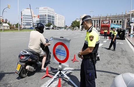 Un agente detiene a un motorista en un control situado en la plaza de Espanya.