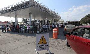 Consumidores esperan por unos litros de gasolina racionada en la ciudad de Moreliaen el estado de MichoacanMexico.EFE Ivan Villanueva