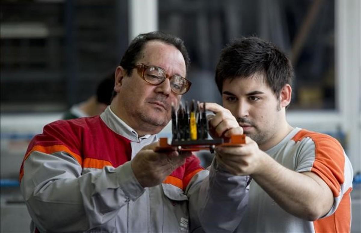 Un profesor de FP dual muestra una pieza de un motor Seat a un alumno.