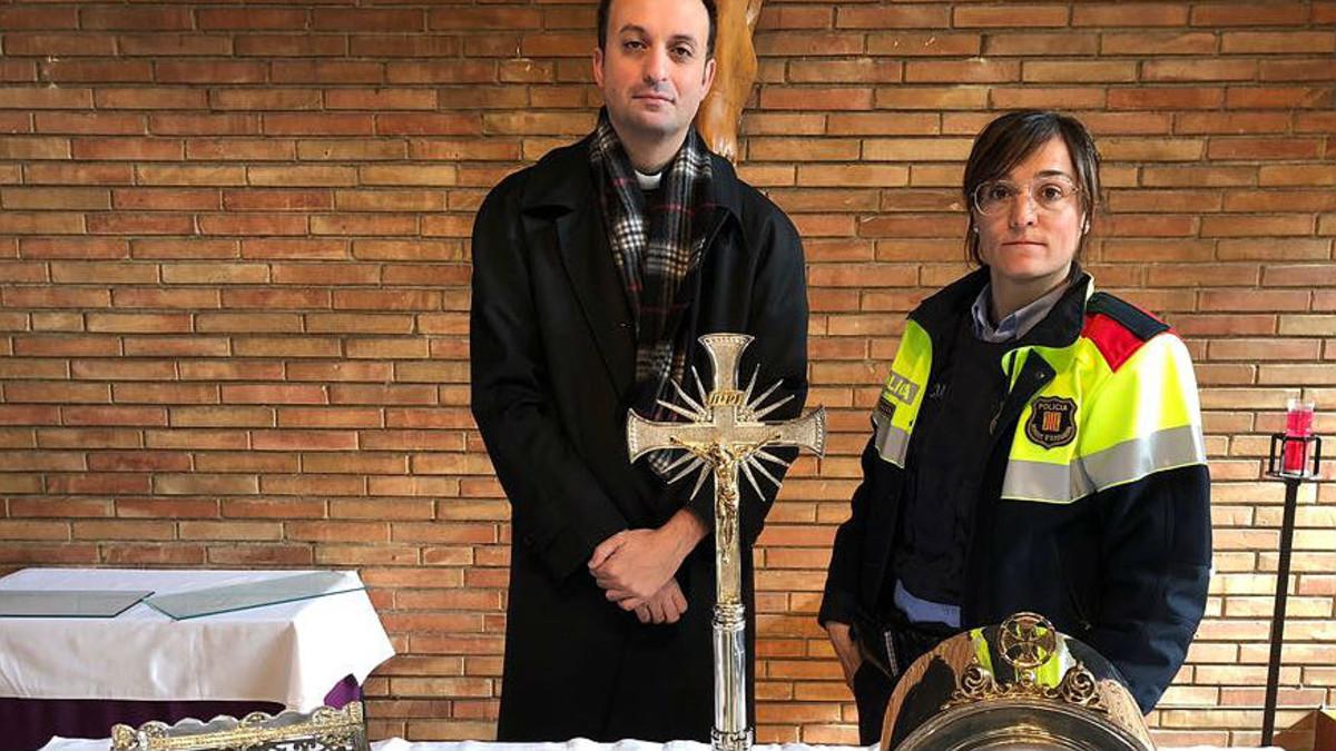 El párroco de Igualada y una agente de los Mossos, con una cruzque debíaser restaurada.