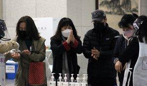 Ciudadanos se desinfectan las manos antes de votar en las elecciones que se celebran en Corea del Sur.